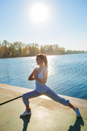 undershirt: young woman in tracksuit and white undershirt   on pontoon at lake practice yoga, sunny autumn day