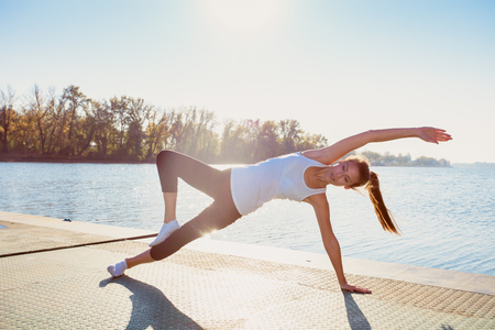 undershirt: young woman in leggings and white undershirt   on pontoon at lake practice yoga, sunny autumn day
