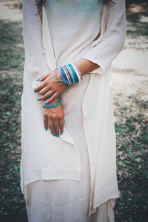turquesa: mujer en vestido largo de algodón con las manos llenas de pulseras de tiro al aire libre, día de verano en el parque, profundidad de campo