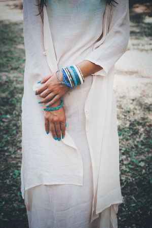 aquamarine: woman in long cotton dress with hands full of bracelets outdoor shot, summer day in park, shallow depth of field