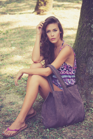 full shot: beautiful young woman wearing thongs and  summer clothes with leather bag sit by tree in wood, full body shot, look at camera, summer day