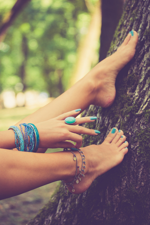 lean on hands: barefoot female feet and hand with boho style bracelets and ring, lean on tree, closeup, selective focus Stock Photo