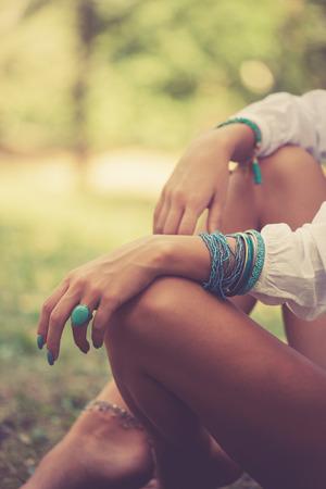 ターコイズ リング、ブレスレット女性手に座って裸足木材、クローズ アップ、暖かい夏の日、選択と集中、芝生の上