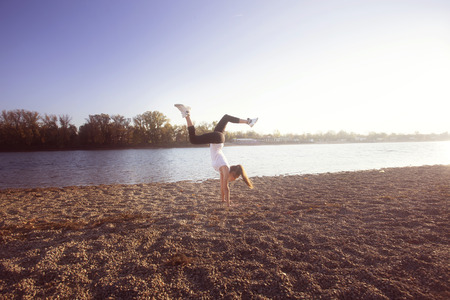handstand: girl exercise by the lake sunny autumn day, full body shot, handstand Stock Photo