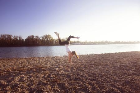 full shot: girl exercise by the lake sunny autumn day, full body shot, handstand Stock Photo