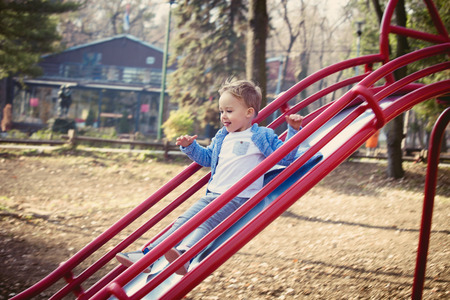 niños rubios: deslizando hacia abajo es una gran sensación, niño pequeño deslizamiento en patio en parque, día de otoño, foco selectivo, foto de cuerpo entero