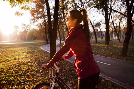 healthy path: the sun gives us energy, girl on bike at park looking at sun, side view