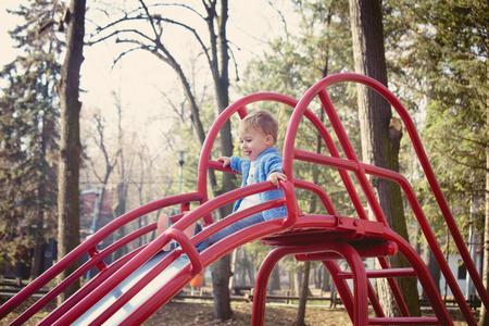 niños rubios: la vida es diversión, niño pequeño se preparan para bajar el tobogán en patio en parque, día de otoño, el enfoque selectivo