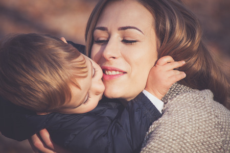 openness: his mom is his greatest love, son and mom kissing and hugging, autumn day in park, closeup, selective focus