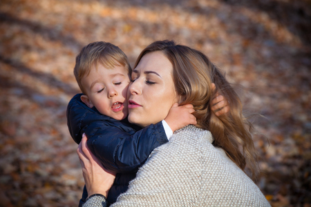madre e hijo: Te amo mamá, joven madre con su pequeño hijo en el abrazo, el día de otoño en el parque, de cerca