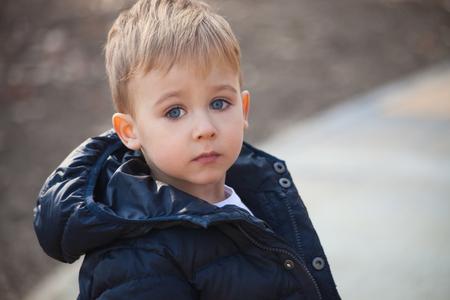 ojos azules: niño lindo con los ojos azules en la chaqueta de invierno al aire libre retrato, foco selectivo