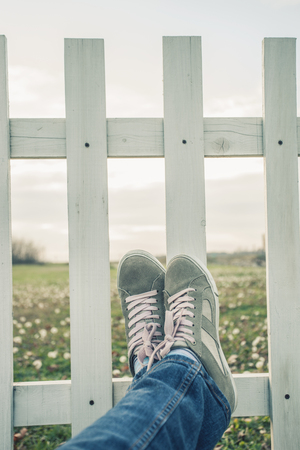 don't care: escape from city, woman legs in jeans and sneakers lean on wooden fence in countryside, relaxing, focus on sneakers