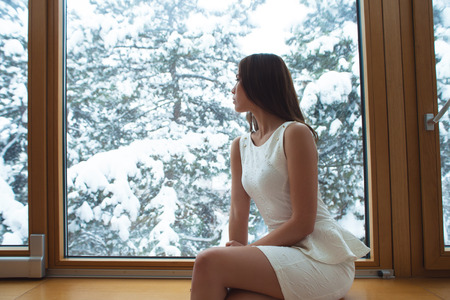 elegant young woman in white short dress sit at home by the window looking snow fall through the glass photo