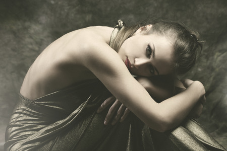 long depression: beautiful young sensual woman in elegant dress sit with wrap  arms around legs,  studio shot, small amount of grain added