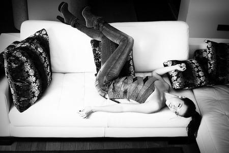 jeans apretados: mujer joven y atractiva en pantalones vaqueros apretados y la parte superior, se encuentran en el sofá de cuero, disparo de cuerpo completo, foto blanco y negro Foto de archivo