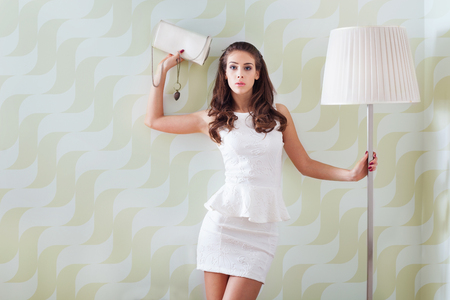 ready to go out, elegant young  woman in  short white dress and purse lean on wall in room  front view