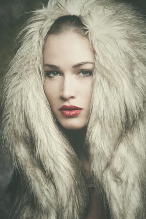 fur: winter is coming, beautiful young woman with artificial fur hood portrait, studio shot, closeup Stock Photo