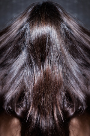 hair back: beautiful dark shiny long woman hair in motion, back view, studio shot