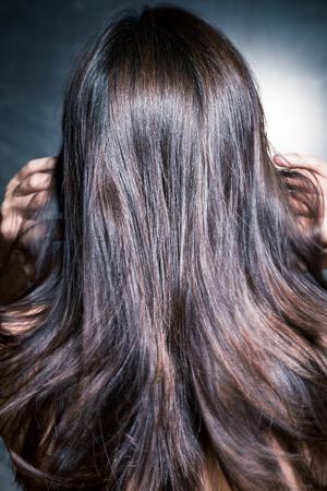 pelo largo: hermosa y brillante mujer de pelo largo y oscuro en movimiento, vista posterior, tiro del estudio