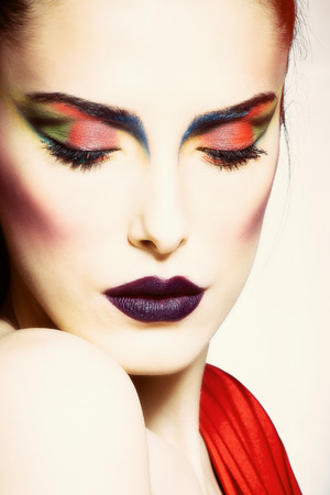 red and blue: young woman with creative colorful makeup, front view, studio shot, close up Stock Photo
