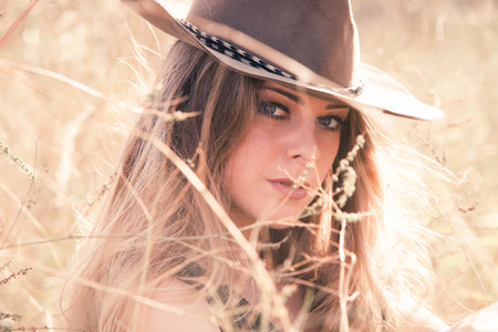 young blonde girl with cowboy hat outdoor in grass, summer day, closeup
