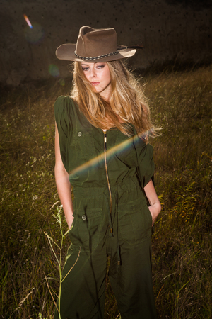 girl in a hat: young blonde girl with cowboy hat outdoor in grass, summer day