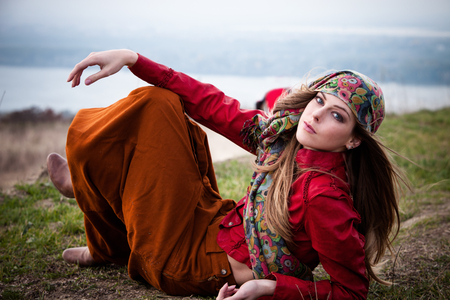 young blonde fashion girl lie on top of hill wearing scarf, long brown skirt and red leather jacket full body shot