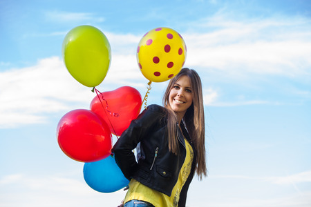ordinary woman: smiling young ordinary  woman in blue jeans and leather jacket  with balloons outdoors against sky Stock Photo