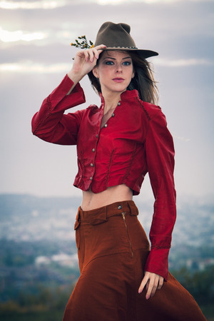 brown leather hat: young blonde fashion girl with hat on top of hill wearing long brown skirt and red leather jacket