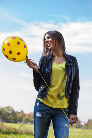 ordinary: smiling young ordinary  woman in blue jeans and leather jacket  with balloon outdoors against sky Stock Photo