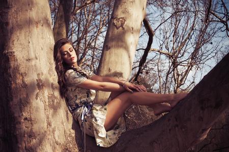 mujer sentada: joven mujer descalza en el resto romántico vestido de verano en copas de los árboles, la luz natural cálido día de verano, foto de cuerpo entero Foto de archivo