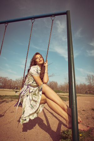 full shot: barefoot young woman sit on swing in summer dress  full body shot, retro colors Stock Photo