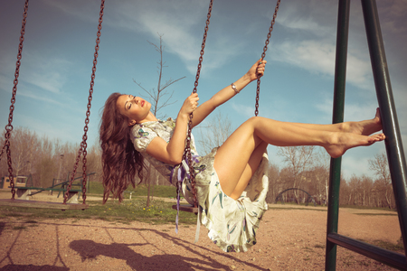 sit: barefoot young woman sit on swing in summer dress  full body shot, retro colors Stock Photo