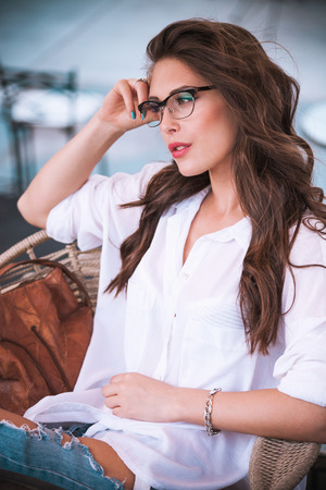 young woman wearing eyeglasses sit and relax in cafe outdoor natural light Standard-Bild