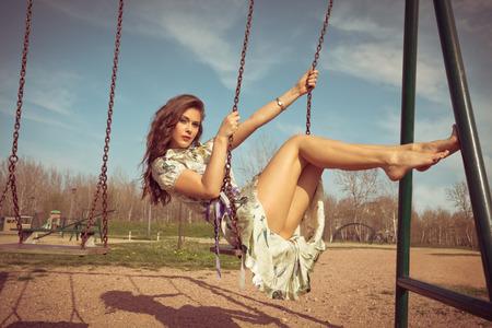 piedi nudi di bambine: a piedi nudi giovane donna si siede su altalena in abito estivo pieno colpo di corpo, i colori retrò