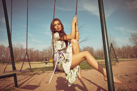 swings: barefoot young woman sit on swing in summer dress  full body shot, retro colors Stock Photo