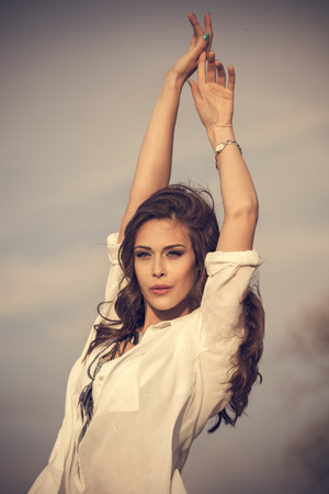 woman white shirt: young woman in white shirt  with arms up stand in wind, natural light, outdoor summer day