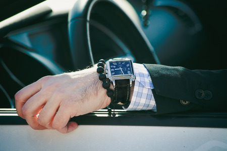 lean on hands: man hand in elegant suit with watch and bracelet lean on car window, closeup natural light, shallow depth of field