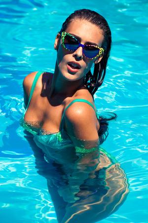 refrescar: Mujer joven feliz en el día de refresco piscina de verano, la luz natural