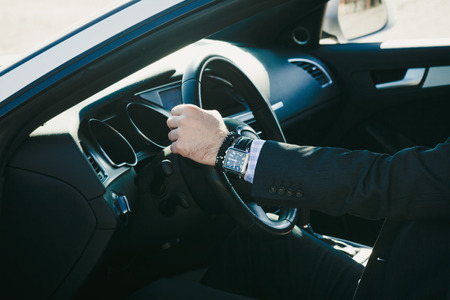 driver: elegant man in suit sit in his car, closeup, natural light, shallow depth of field Stock Photo