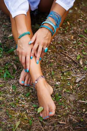 woman barefoot: woman hands on barefoot feet with lot of bracelets in turquoise color sit on ground from above shot Stock Photo