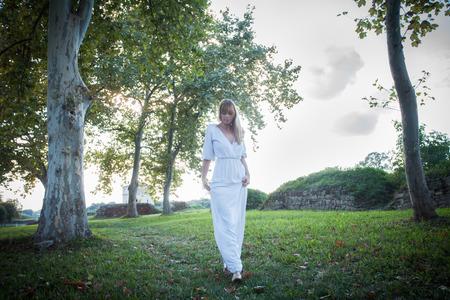 full shot: woman in long white dress walk among trees in park, natural light, full body shot Stock Photo