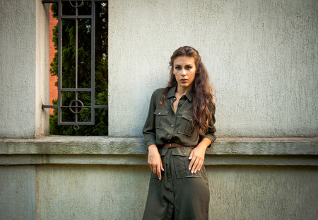 style woman: young woman in military style fashion dress lean on wall, day shot, natural light Stock Photo