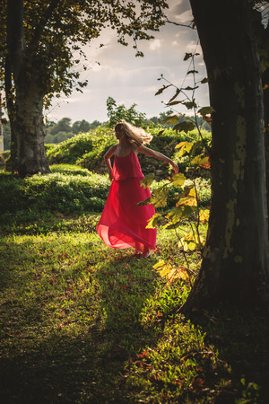 day light: young woman in long red dress run  through the woods, summer day, natural light, full body shot