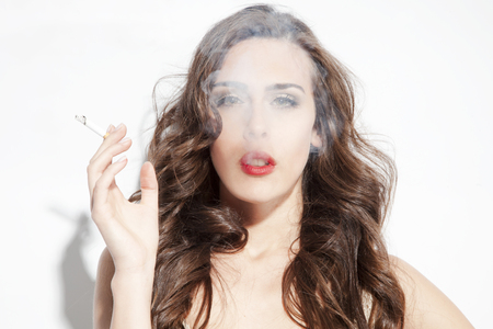 young woman smoking cigarette with smoke in front of her face