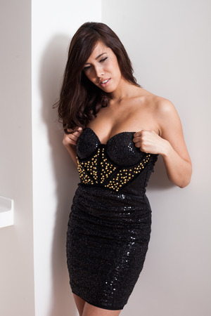 elegant young woman in black cocktail dress prepare to go out, indoor shot photo