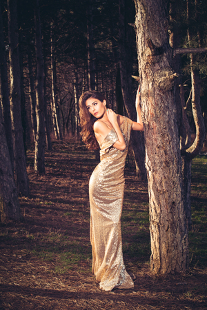 full shot: beautiful young woman in elegant glittering golden dress  in wood full body shot