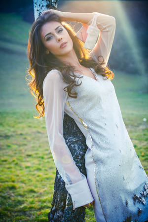 outdoor shot: elegant young woman in white dress outdoor shot winter day