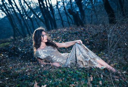 glamor: beautiful young woman in elegant glittering  dress  in wood lie on leaves full body shot