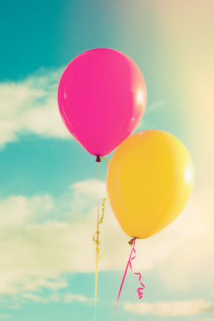 love shape: pink and yellow balloons against sky with clouds, closeup